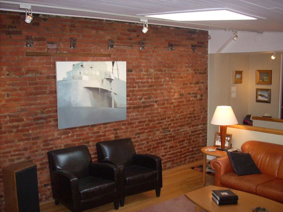 Original exposed brick wall in living room. Leather sofa is a fold-out queen bed.