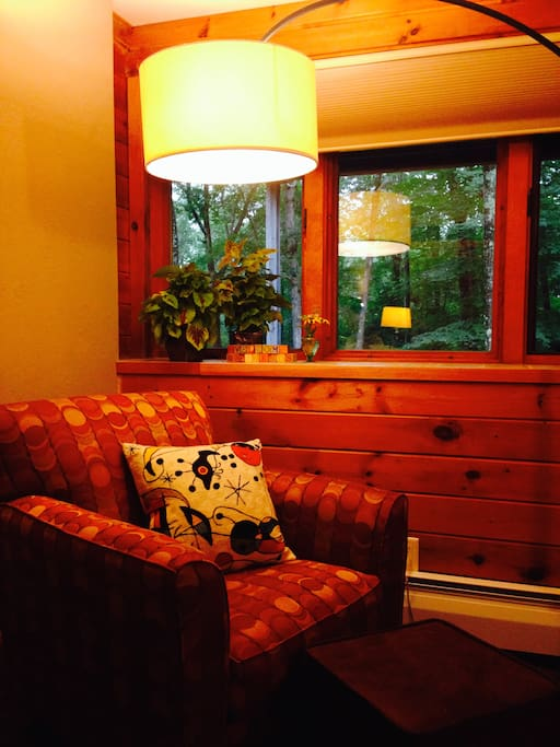 Your bedroom has a comfy seat that next to a bank of windows looking out into the forest.