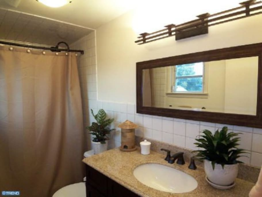 Large Clean Bright Full Bathroom with tumbled marble floor and granite countertop
