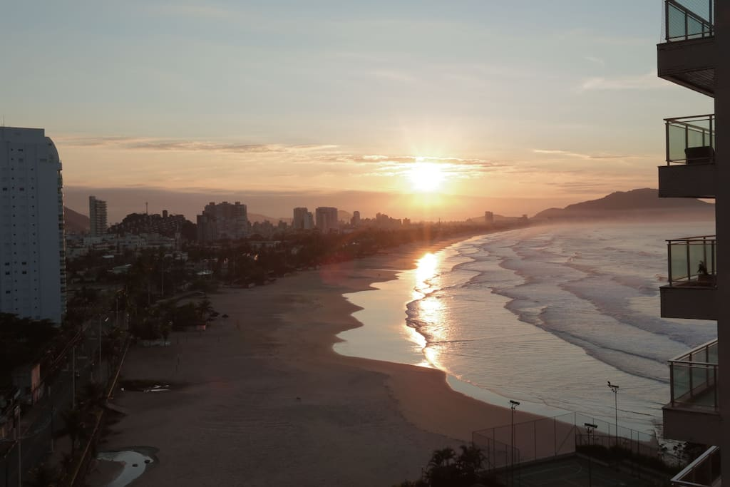Vista do apartamento para a praia da Enseada com o sol nascendo.