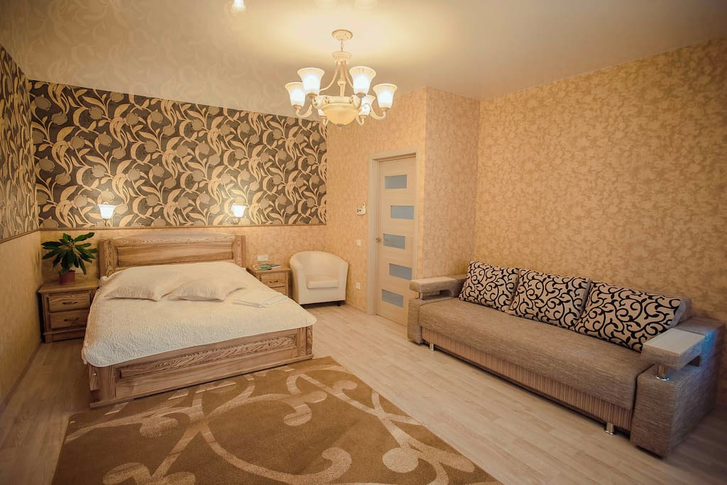 В комнате стоит широкая двухспальная кровать и мягкий диван