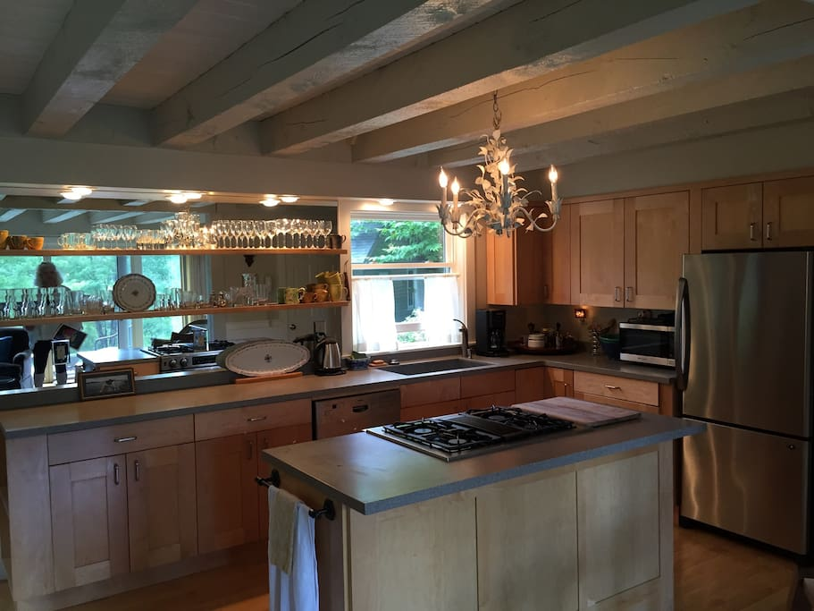Country yet modern kitchen with new appliances: dishwasher, sink, stove, refrigerator, microwave