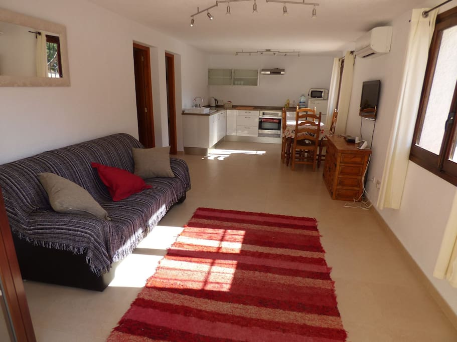 Taken from Apartment entrance, large sofa, TV, Dining table and large kitchen area, with Air conditioning