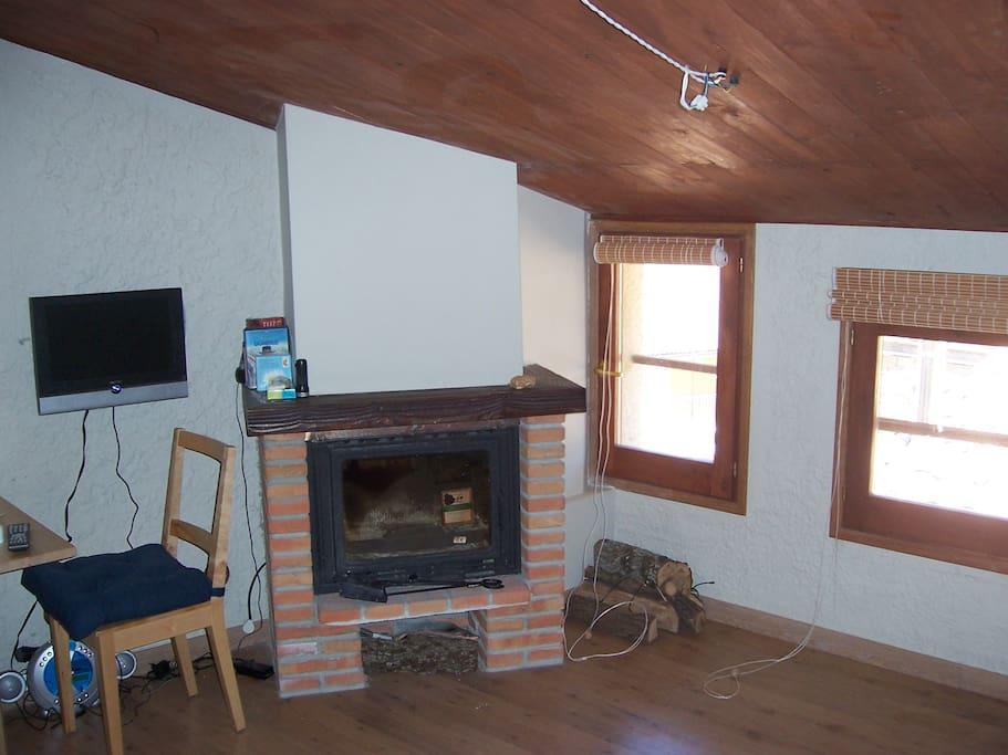 Salón comedor con chimenea hermética, mesa, sofá cama, TV, y sillas
