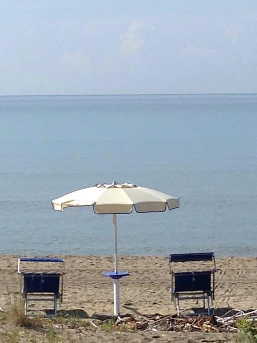 Ombrellone e lettini che vi attendono sulla spiaggia in alta stagione
