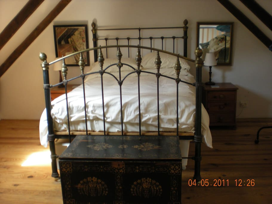 Cozy bedroom with brass bed, french windows and Juliette balcony.