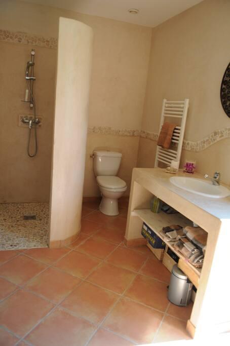 Salle de bain privée avec douche à l'italienne en tadelakt, wc, lavabo et sèche-serviettes