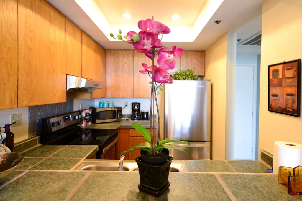Fully equipped kitchen with stone countertops, wooden cabinets, and stainless steel appliances