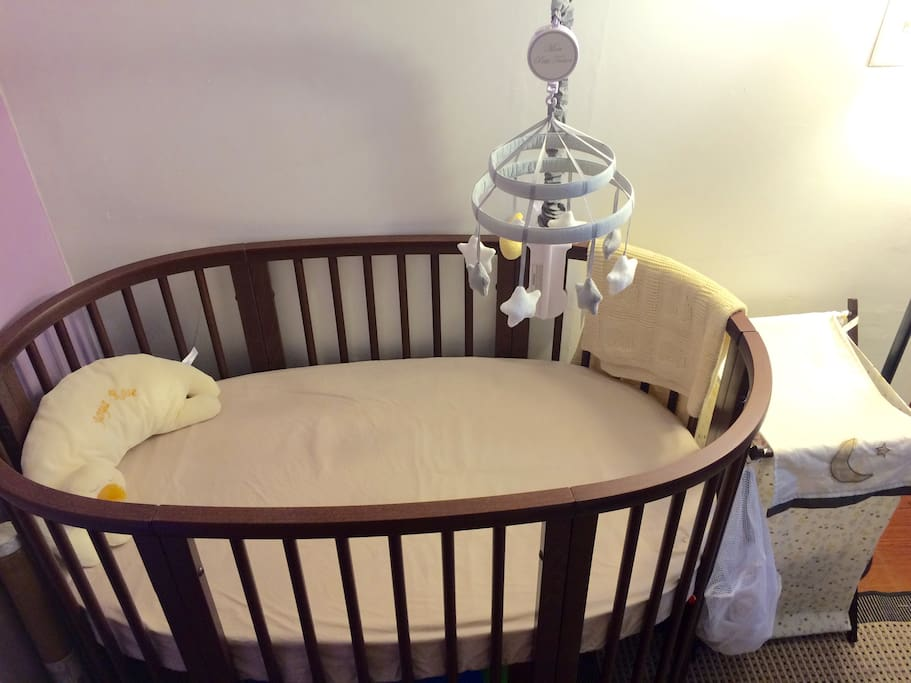 Beautiful Stokke crib with musical mobile and laundry basket.