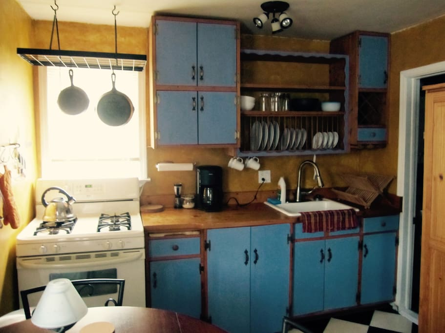 French farmhouse style kitchen with wood counter, microwave, gas stove/oven, blender, coffee pot, cast iron pans, and everything you'll need to make a gourmet meal!