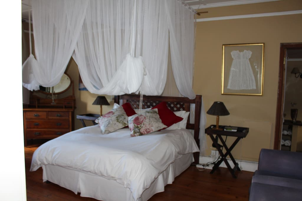 Diamond room with queen bed, TV, laptop table and chair, and comfortable chairs. Outside access available.