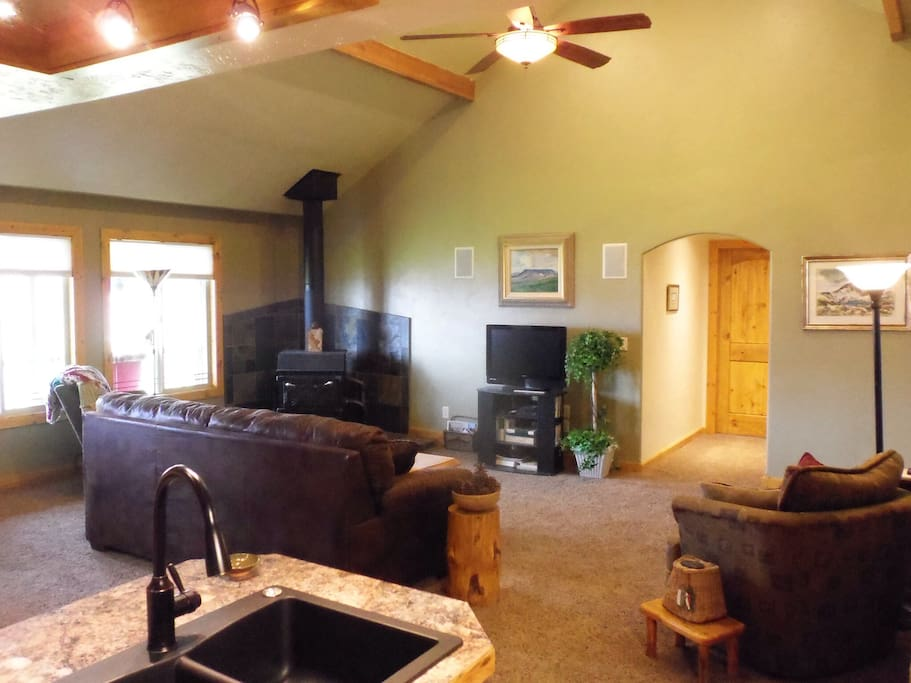 Another view of the living room showing the vaulted ceiling and the wood stove.
