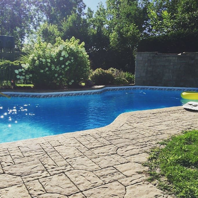 Private oasis in the backyard. Large property completely secluded by 20ft cedar hedges and backing into green space. Heated, salt water pool with waterfall at your disposal. 40 ft long with a diving board, relax on air mattresses or play for days. Pool to