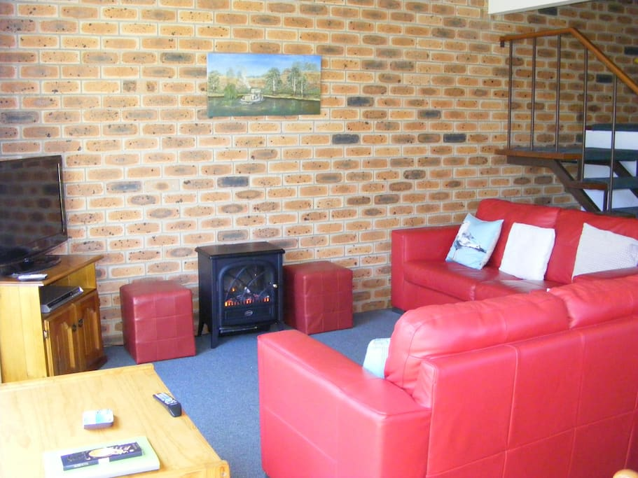 Comfy leather lounges with electric log heater, flat screen tv and dvd player.