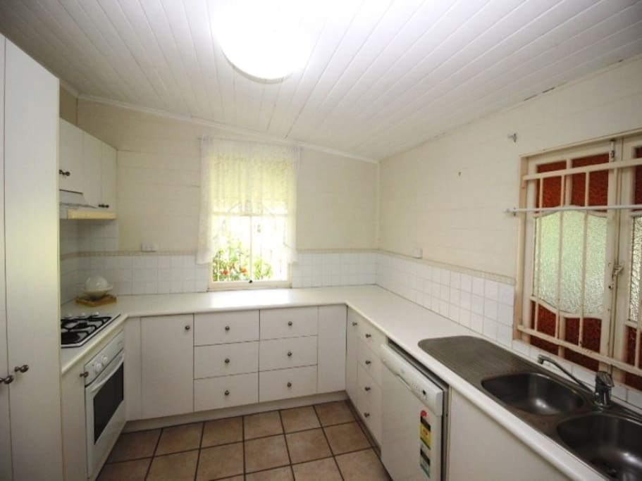 Spacious kitchen with gas stovetop and dishwasher.