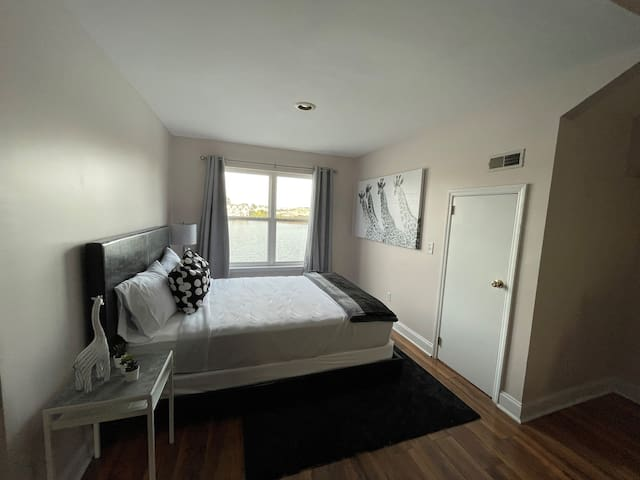 Third floor bedroom joins the second living space for guests with a queen size bed.