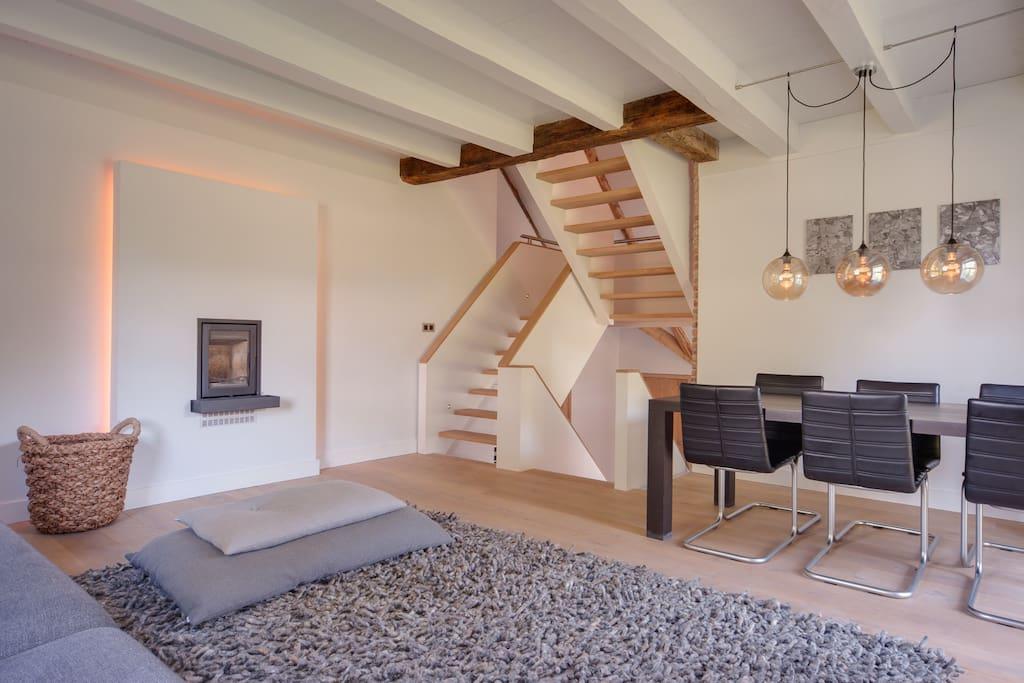 Opkamer met houtkachel, lcd-tv, hifi-systeem en eettafel voor zes personen.