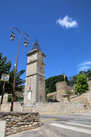 L'horloge du village avec, en arrière plan, une tour des remparts du château