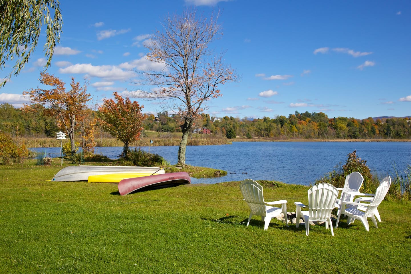 Lake facing view of Adirondack chairs around camp fire.  Row boat, kayak and canoe usage included with rental.
