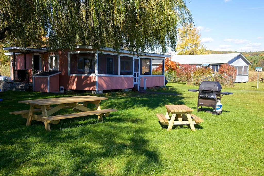 Front view of camp with large screened in porch, grill and picnic tables.