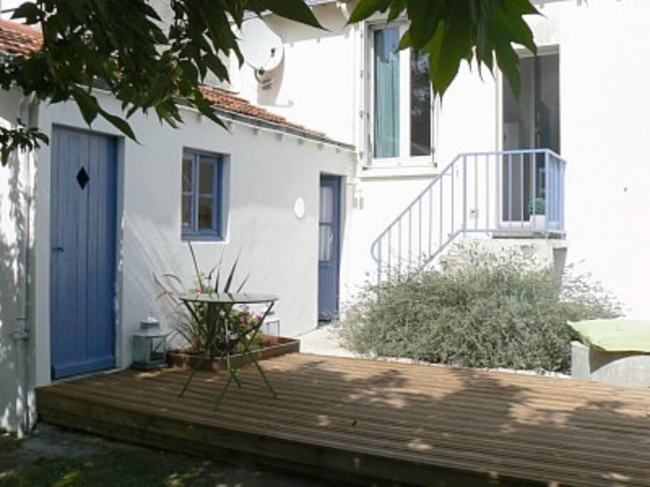 En bas de l'escalier la salle de bain extérieure et la terrasse du jardin.