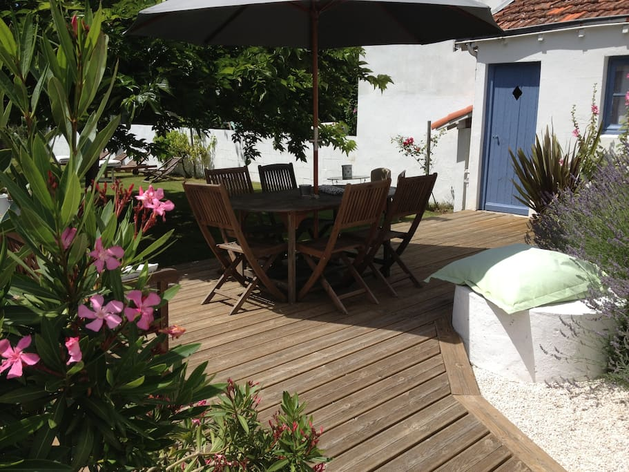 Arrivée sur la terrasse en bois avec son parasol et la table avec 6 chaises en bois.