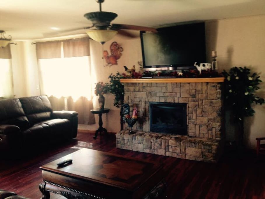 Living room consists two couches with recliner, gas fireplace, large screen TV with Direct TV.