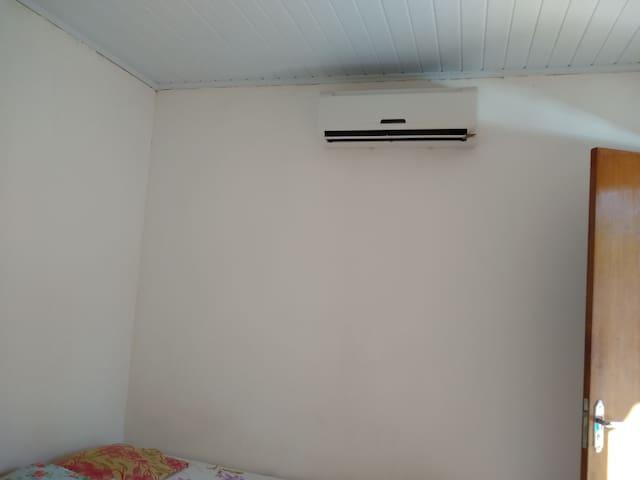 Ar split do quarto A, com cama de casal, cama de solteiro, criado mudo, banheiro completo e berço desmontável.