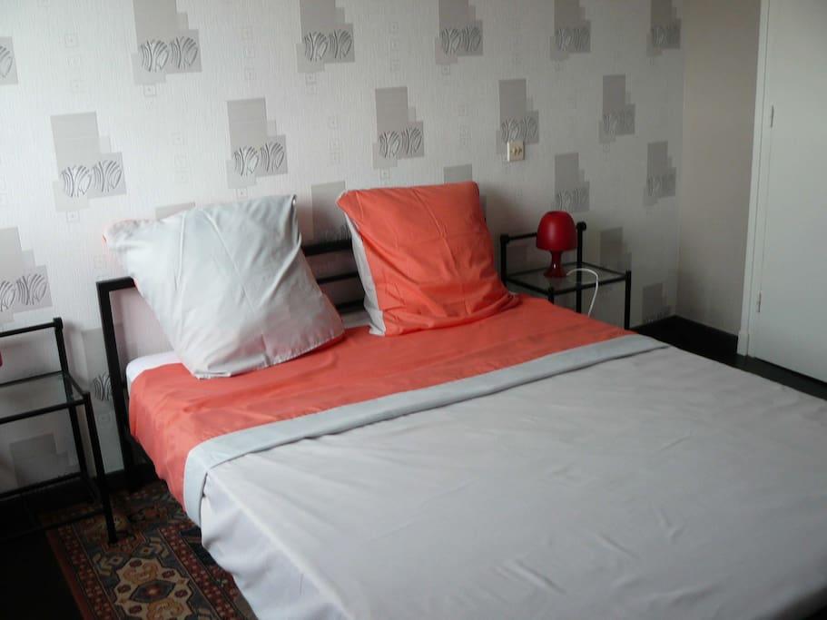 chambre spacieuse avec un grand lit en 140