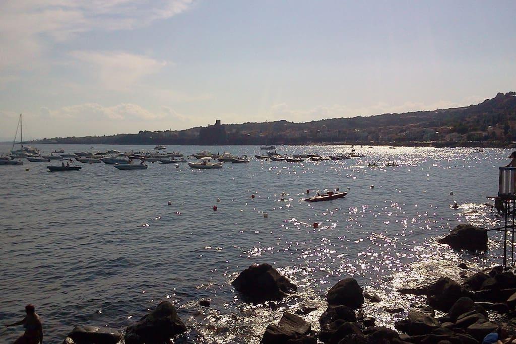 Campo boe di fronte la discesa a mare, con nello sfondo la costa di Acitrezza sovrastata dal castello normanno di acicastello.
