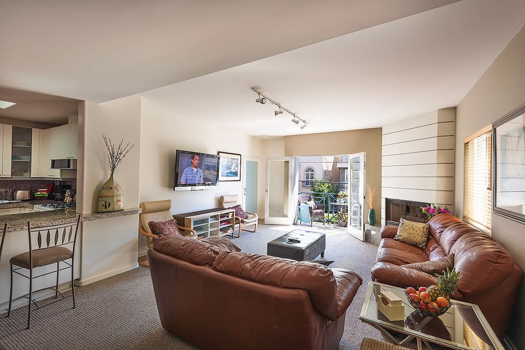 This spacious living room has plenty of seating, fireplace, wall-mounted flat-screen TV, carpeted floors and opens up to the private patio.Living Room