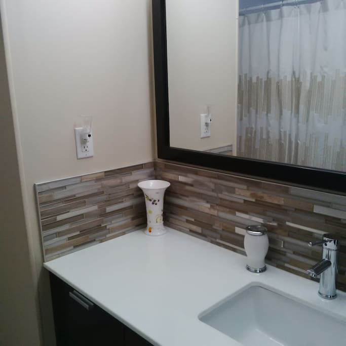 New backsplash and mirror. Shower curtain is reflected in mirror.