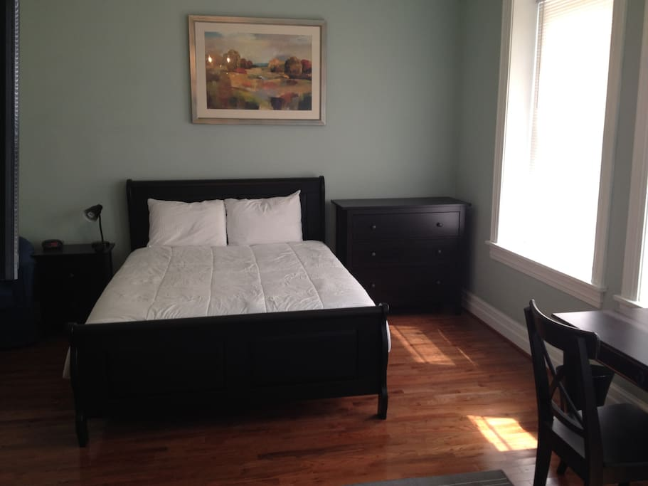 Queen size bed in a very spacious room with high ceilings and plenty of natural light