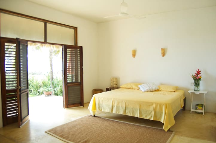 Master Bedroom with king size bed, en suite bath,  with view to the beach and pool