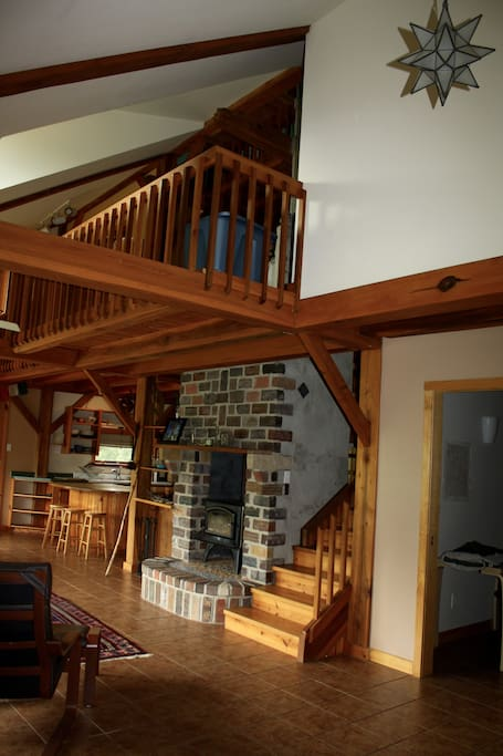 Entry way, cathedral  ceilings, wood stove and steps to upstairs