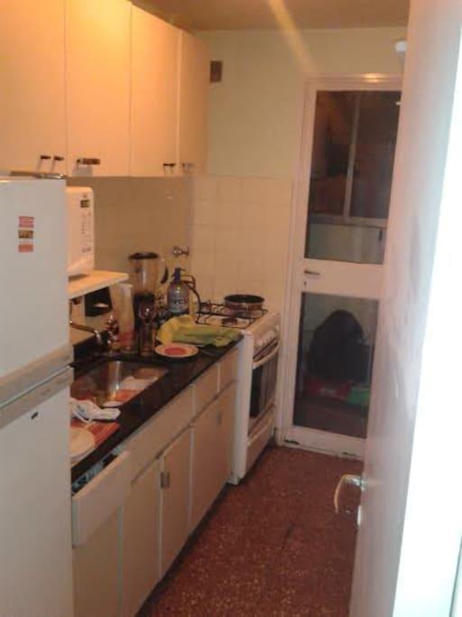 cocina con microondas, salida al lavadero y balcon