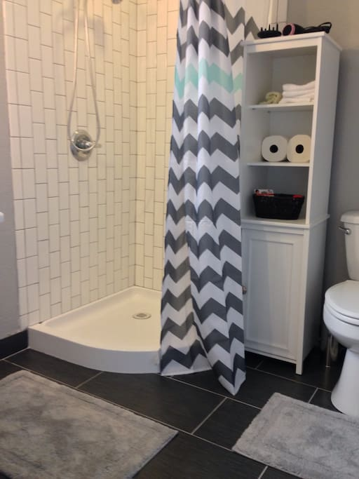 Modern bathroom with large pedestal sink, subway-tiled shower stocked with plush towels, sulfate-free shampoo, conditioner and body wash, lighted magnifying makeup mirror, and ionic hair dryer.