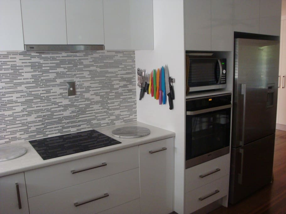 Induction cook-top, range-hood, convection microwave and fridge with iced water and ice maker.