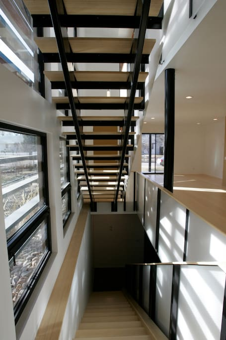 Stairs to bedroom in the lower level that has high ceilings and a large windows.