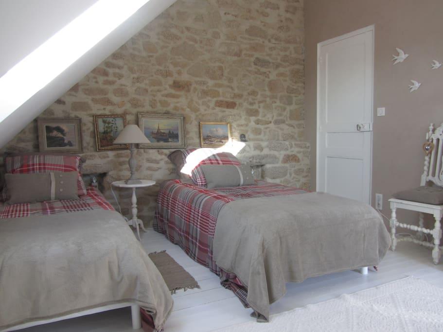 Deux lits jumeaux qui peuvent être rapprochés pour constituer un grand lit de 180 cm.