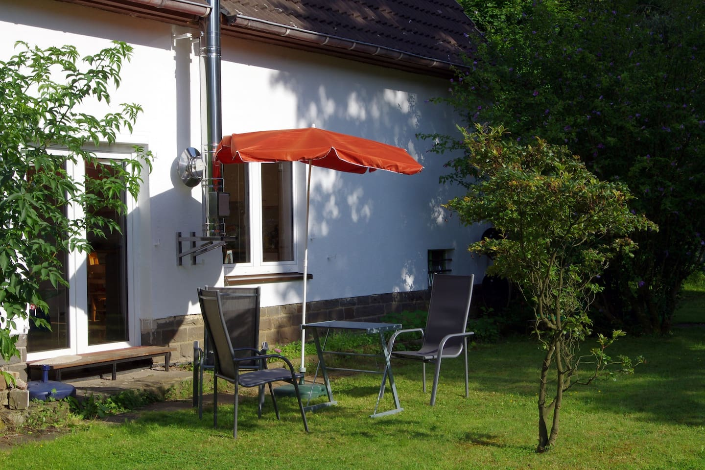Gartenseite, links die Terrassentür zur Wohnung / Seats for guests on the lawn,  on the left: back entrance to the house