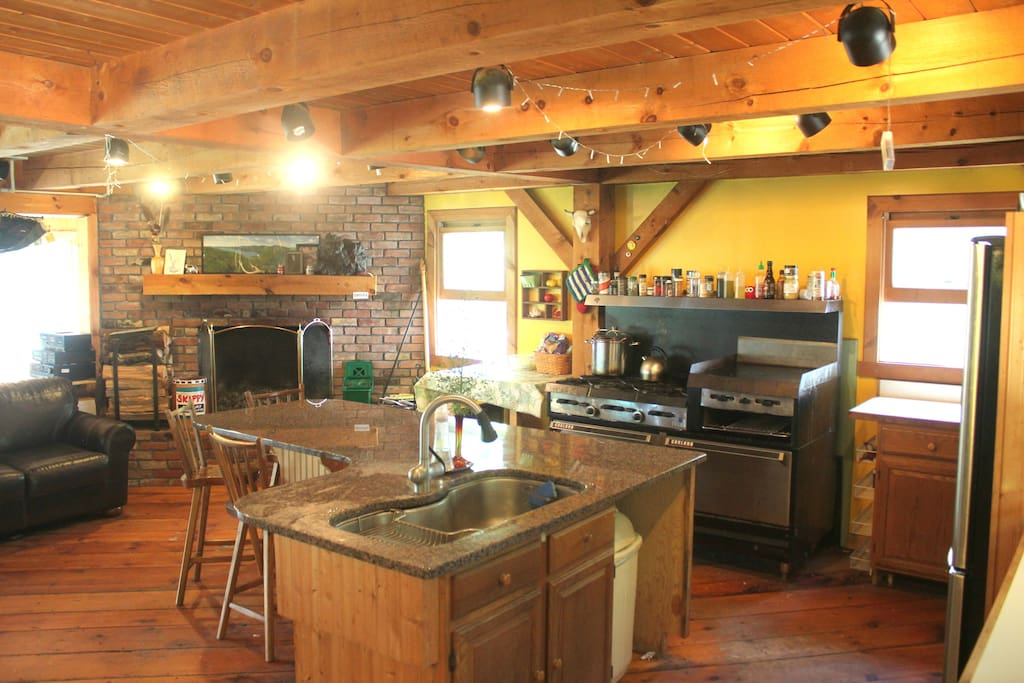 Kitchen with fireplace, industrial stove top, and plenty of counter and hang out space