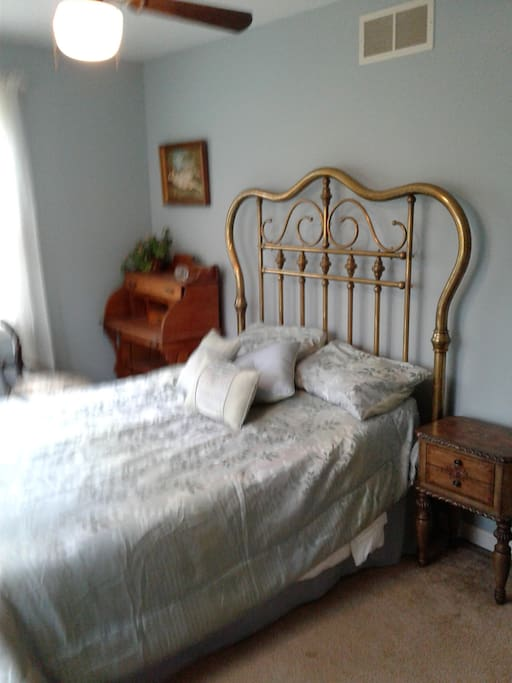 View of antique brass bed, desk, chair and night stand.  Ceiling fan, central heat and a/c.