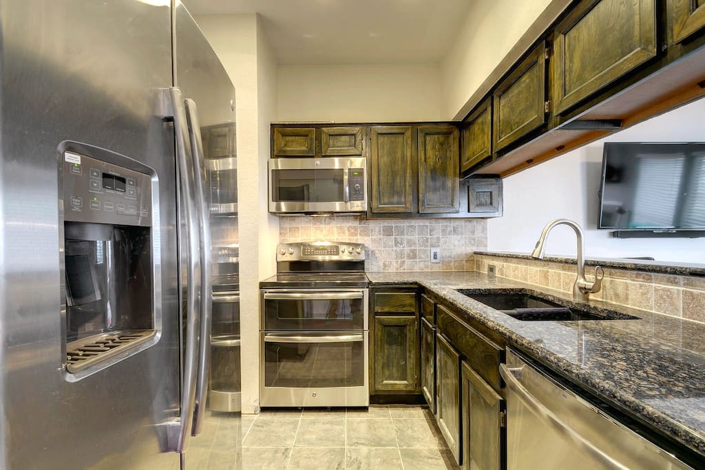 Stainless steel GE appliances and granite counters.