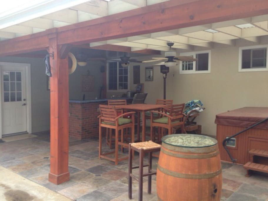 Backyard, spa, bar seating or table, ceiling fans for warm days and heat lamp for cool nights