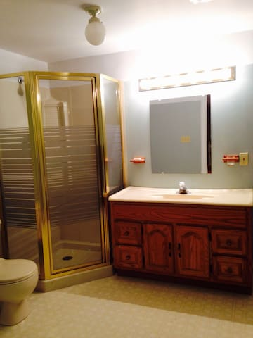 Private bathroom with standing shower unit.