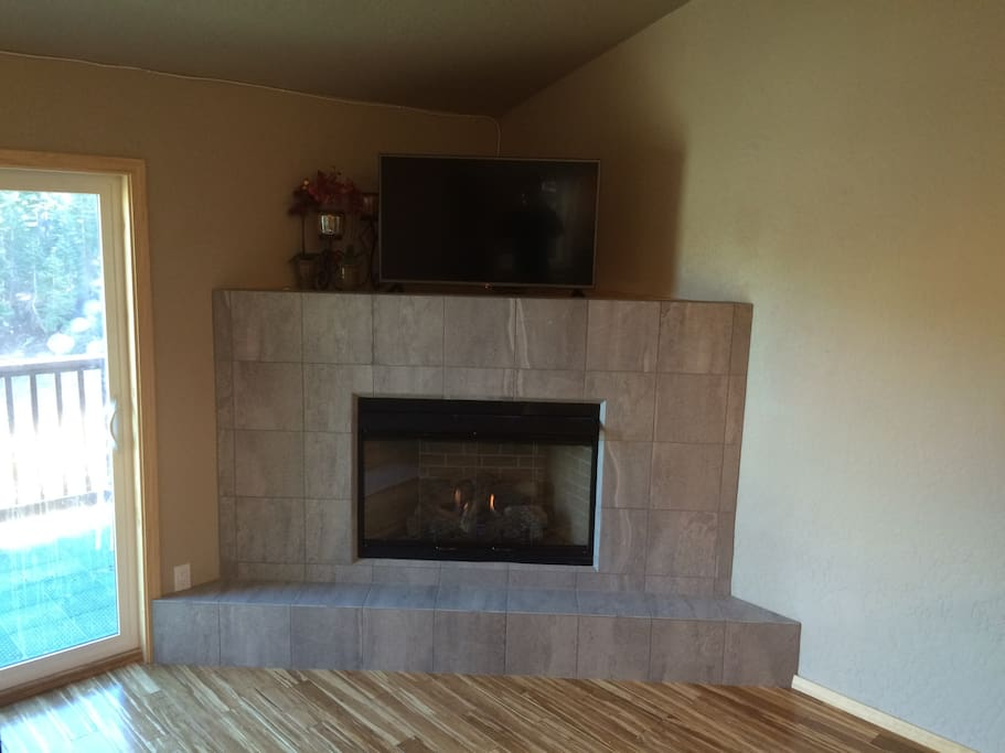 Fireplace  in kitchen/dining room with a 32 inch flat screen TV.
