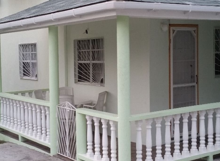 Porch with table and chairs for outside relaxation and dining. Private parking available for guests.