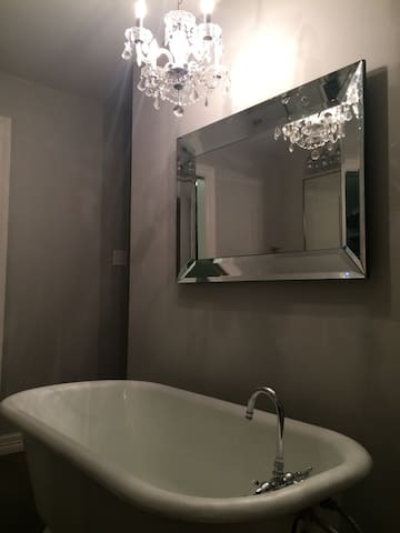 Romantic free standing bath tub with crystal chandelier and private tv.