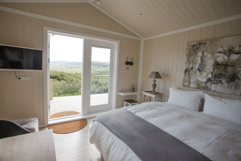 Comfortable bed with high standard pillows and dunes. Nice view outside the bedroom window.